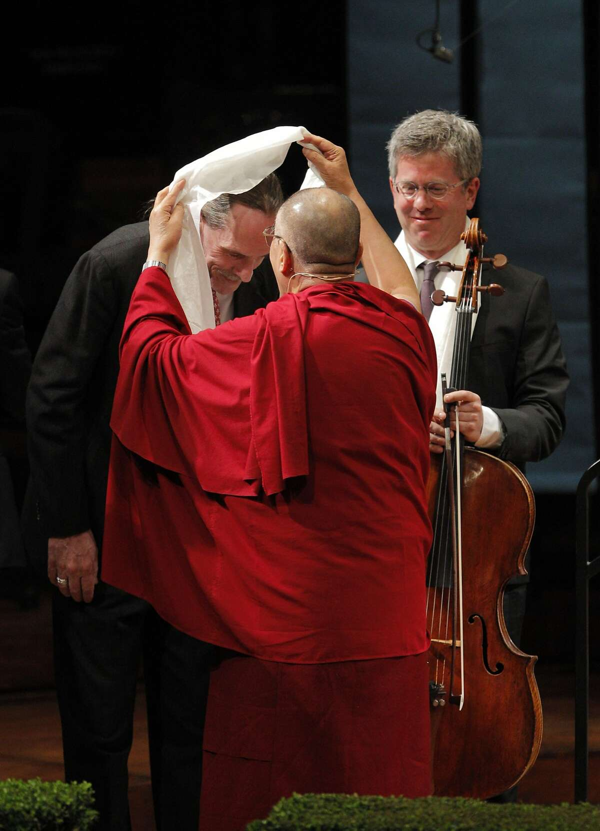 His Holiness the 14th Dalai Lama places a white scarf on pianist Robin Sutherland after His Holiness spoke at Davies Symphony Hall in San Francisco, Calif., on Saturday, February 22, 2014, as part of The American Himalayan Foundation and the Blum Center for Developing Economies at UC Berkeley talk titled �