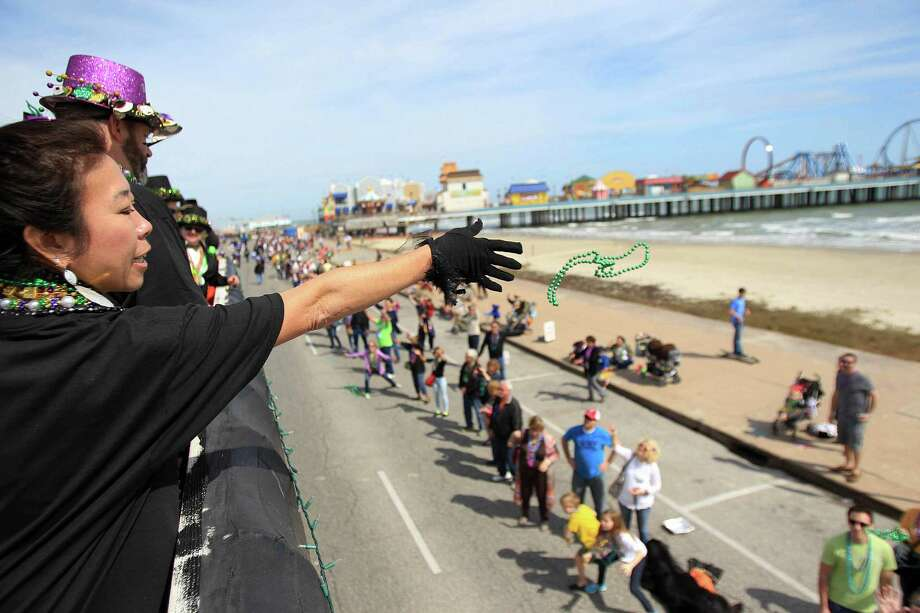 Cindy Jones throws beads during The Mystic Krewe of Aquarius 29th Annual Mardi Gras Parade as it travels along Seawall Blvd. on Saturday, Feb. 22, 2014, in Galveston. Photo: Mayra Beltran, Houston Chronicle / © 2014 Houston Chronicle
