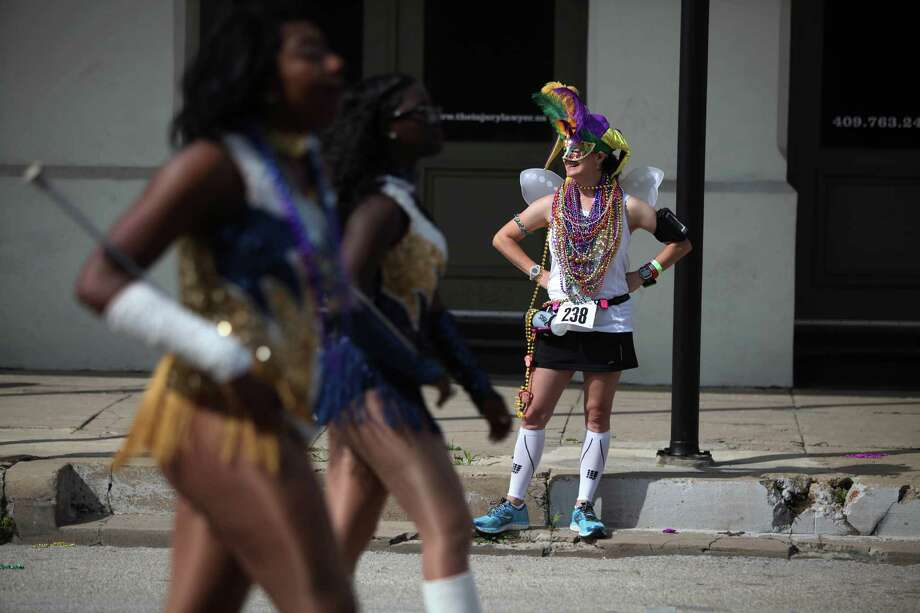 A runner stops to see The Mystic Krewe of Aquarius 29th Annual Mardi Gras Parade in The Strand as it travels through its new route on Saturday, Feb. 22, 2014, in Galveston. Photo: Mayra Beltran, Houston Chronicle / © 2014 Houston Chronicle