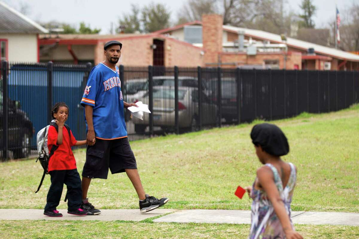 Jimmy Coffman walks with his daughter, Aaniyah Neal, 5, as students are dismissed from Nathaniel Q. Henderson Elementary School Thursday, Feb. 20, 2014, in Houston. Henderson is one of the schools the Houston Independent School District is considering closing.