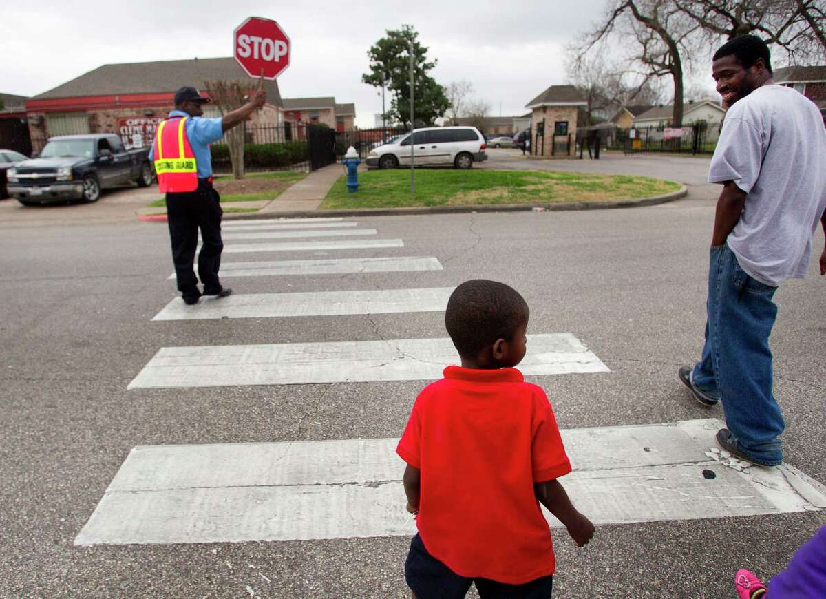 Tremayne Whitfield, Jr., looks to cross the Coke Street with his father, Tremayne Whitfield, Sr., toward the Cleme Manor apartment complex as students are dismissed from Nathaniel Q. Henderson Elementary School Thursday, Feb. 20, 2014, in Houston. Henderson is one of the schools the Houston Independent School District is considering closing.