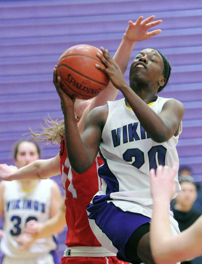 A Greenwich defender's hand in her face is not enough to stop Westhill's Tyler Evans (#20) from scoring during the FCIAC girls basketball quarterfinal between Westhill High School and Greenwich High School at Westhill in Stamford, Saturday, Feb. 22, 2014. Greenwich defeated Westhill, 55-51. Photo: Bob Luckey / Greenwich Time