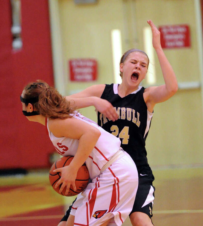 At right, Trumbull's Amanda Pfohl (# 24) of Trumbull reacts after taking an elbow to the nose while defending Alexa Moses of Greenwich during the girls high school basketball game between Greenwich High School and Trumbull High School at Greenwich, Wednesday, Feb. 19, 2014. Photo: Bob Luckey / Greenwich Time