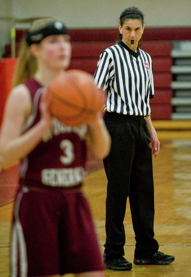 Wooster School's Kate MacNutt is watched during the game by referee Lisa Mikelic, a Danbury High School graduate and a 1000 point scorer in girls basketball. Thursday, Feb. 20, 2014 Photo: Scott Mullin / The News-Times Freelance