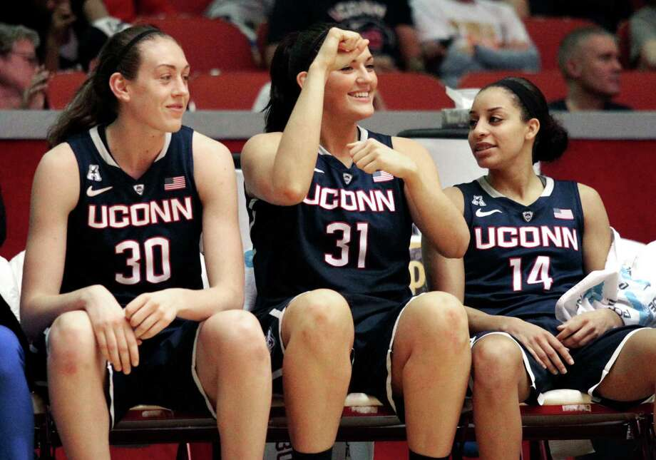 Connecticut's Breanna Stewart , 30, Stefanie Dolson, 31, and Bria Hartley, 14, celebrate on the bench after defeating Houston 92-41  during an NCAA women's basketball game, Saturday, Feb. 22, 2014, in Houston. (AP Photo/Patric Schneider) Photo: Patric Schneider, Associated Press / Associated Press