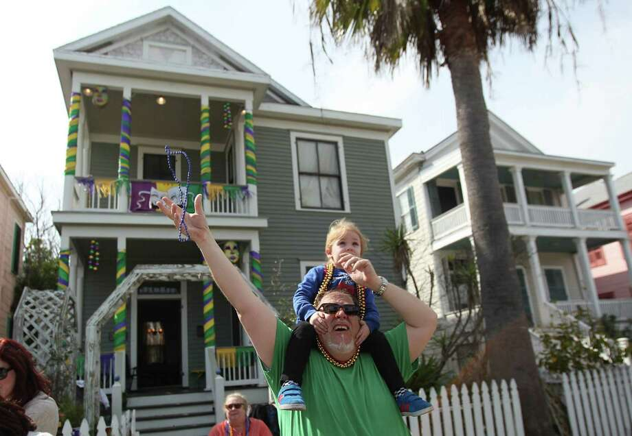 Brian Hicks grabs beads for Elliot Clare Hicks along 25th Street as The Mystic Krewe of Aquarius 29th Annual Mardi Gras Parade travels along the new parade route on Saturday, Feb. 22, 2014, in Galveston. Photo: Mayra Beltran, Houston Chronicle / © 2014 Houston Chronicle