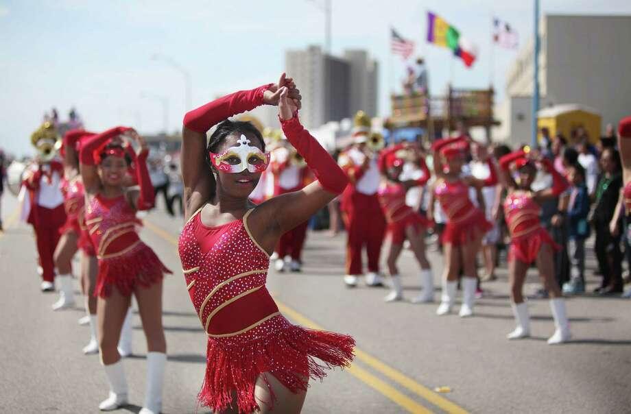 Yates High School dances along Seawall Blvd. during The Mystic Krewe of Aquarius 29th Annual Mardi Gras Parade on Saturday, Feb. 22, 2014, in Galveston. Photo: Mayra Beltran, Houston Chronicle / © 2014 Houston Chronicle