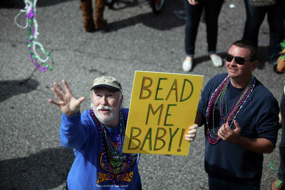 An unidentified man reaches out for beads as The Mystic Krewe of Aquarius 29th Annual Mardi Gras Parade travels along Seawall Blvd. on Saturday, Feb. 22, 2014, in Galveston. Photo: Mayra Beltran, Houston Chronicle / © 2014 Houston Chronicle