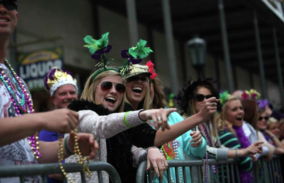 Spectators share a laugh as floats make their way through The Strand during The Mystic Krewe of Aquarius 29th Annual Mardi Gras Parade on Saturday, Feb. 22, 2014, in Galveston. Photo: Mayra Beltran, Houston Chronicle / © 2014 Houston Chronicle