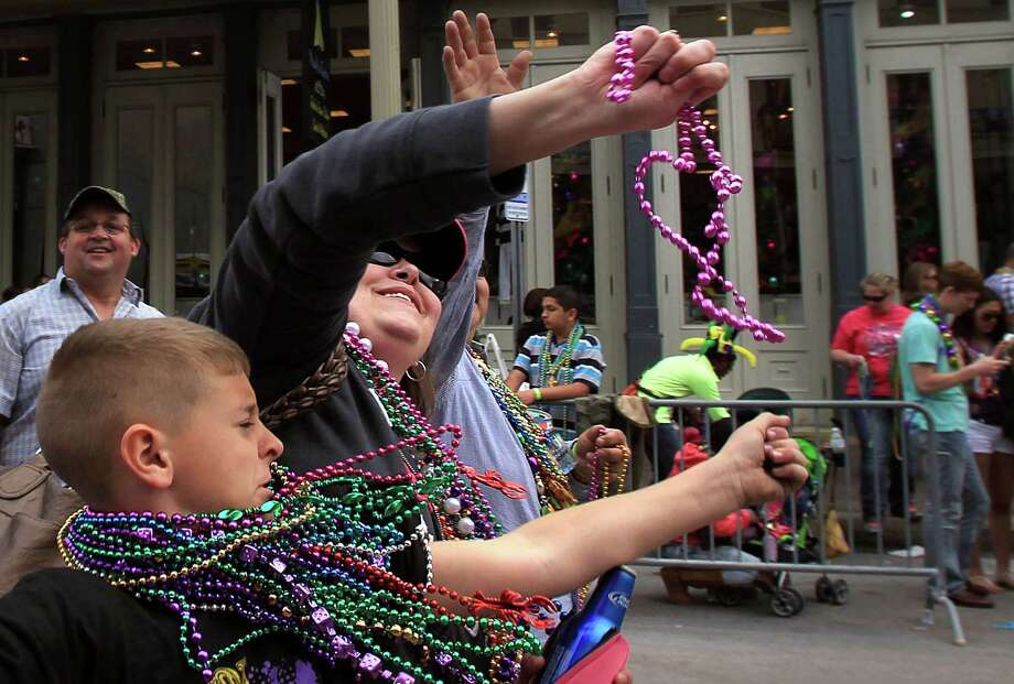 Trisha Turner grabs beads thrown from a balcony in The Strand upon the conclusion of The Mystic Krewe of Aquarius 29th Annual Mardi Gras Parade on Saturday, Feb. 22, 2014, in Galveston. Photo: Mayra Beltran, Houston Chronicle / © 2014 Houston Chronicle
