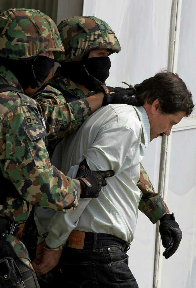 """Joaquin """"El Chapo"""" Guzman is escorted to a helicopter in handcuffs by Mexican navy marines at a navy hanger in Mexico City, Saturday, Feb. 22, 2014. A senior U.S. law enforcement official said Saturday, that Guzman, the head of Mexicoés Sinaloa Cartel, was captured alive overnight in the beach resort town of Mazatlan. Guzman faces multiple federal drug trafficking indictments in the U.S. and is on the Drug Enforcement Administrationés most-wanted list.  (AP Photo/Dario Lopez-Mills) Photo: Dario Lopez-Mills, STF / AP"""