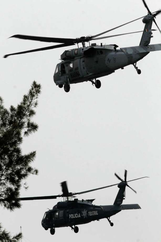 "A Mexican navy helicopter, top, escorts a federal police helicopter transporting Joaquin ""El Chapo"" Guzman, after taking off from the Navy hanger in Mexico City, Mexico, Saturday, Feb. 22, 2014.  The world's most-wanted drug lord, Guzman, arrived at the Mexico City airport after his arrest early Saturday and was being taken directly to prison, said Attorney General Jesus Murillo Karam.  Photo: Marco Ugarte, STR / AP"