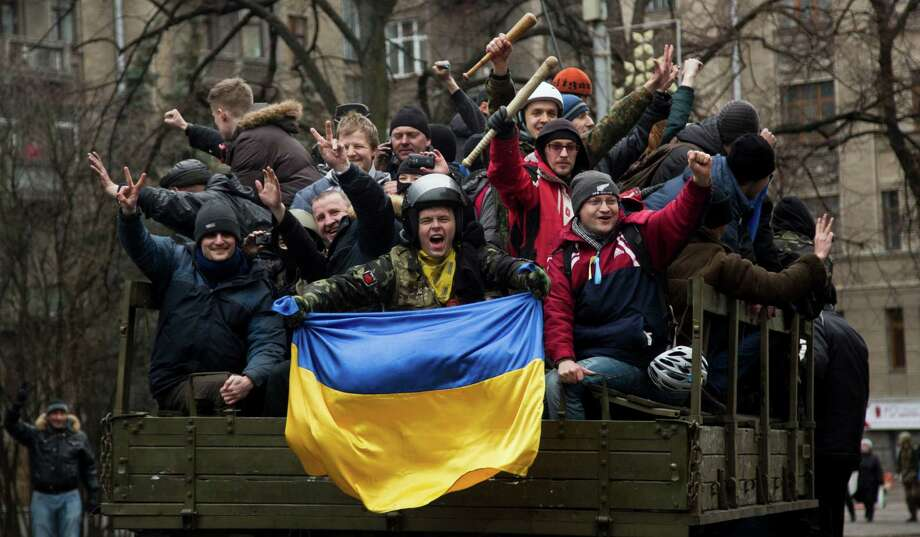 Protesters celebrate as they ride atop a truck in Kiev on Saturday. But the protesters' joy could be brief if the nation, already splintering, slides into turmoil. Photo: Darko Bandic, STF / AP