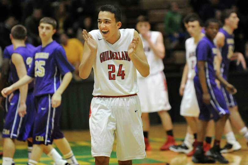 As the clock winds down, Guilderland's Ralph Simeone, center, celebrates their Class AA basketball q