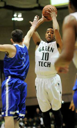 Green Tech's Jizziah Carr, right, shoots for the hoop as Shaker's Seamus McHugh defends during their