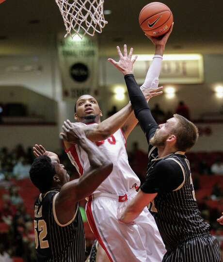 Houston's TaShawn Thomas goes up for two of his 11 points over Central Florida's Kasey Wilson, left, and Staphon Blair in Saturday's game at Hofheinz Pavilion. Photo: Bob Levey / ©2014 Bob Levey