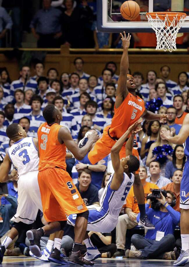 Duke's Rodney Hood (5) draws a charge from Syracuse's C.J. Fair (5) as Syracuse's Jerami Grant (3) and Duke's Tyler Thornton (3) stand near late in the second half of an NCAA college basketball game in Durham, N.C., Saturday, Feb. 22, 2014. Duke won 66-60. (AP Photo/Gerry Broome) ORG XMIT: NCGB113 Photo: Gerry Broome / AP