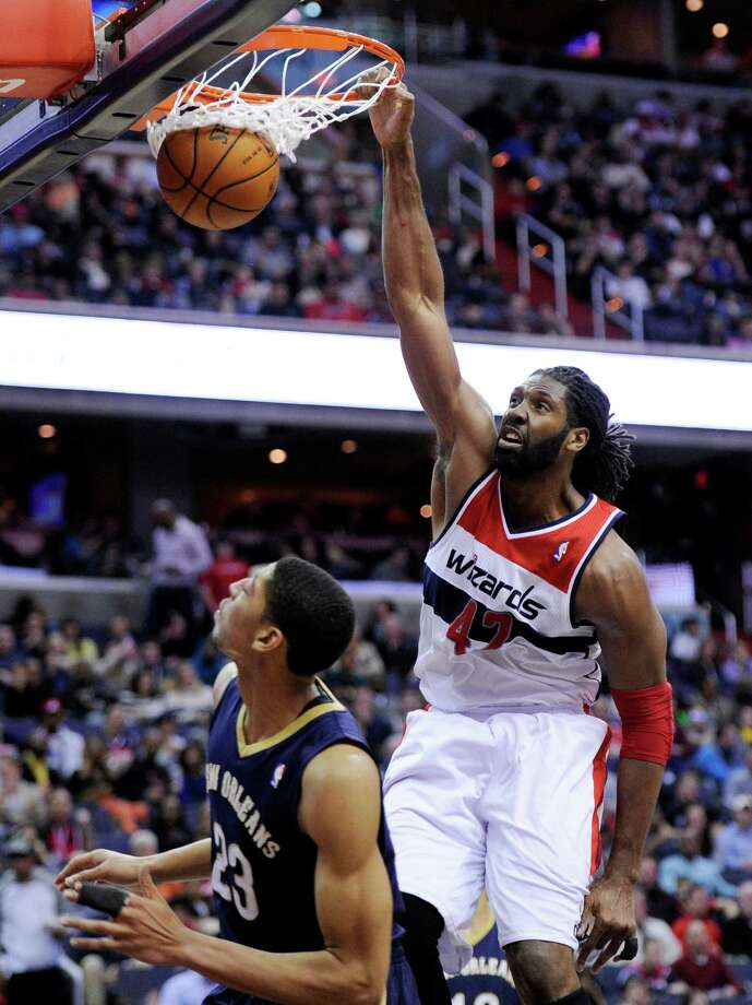 Washington Wizards forward Nene (42), of Brazil, dunks over New Orleans Pelicans forward Anthony Davis (23) during the second half of an NBA basketball game, Saturday, Feb. 22, 2014, in Washington. The Wizards won 94-93. (AP Photo/Nick Wass) ORG XMIT: VZN126 Photo: Nick Wass / FR67404 AP