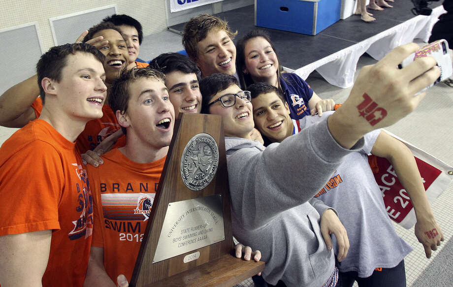 The Brandeis boys swimming team poses for a selfie with their Class 5A runner-up trophy at UT's Jamail Center in Austin. Aaron Brysch earned a state title in the 100-yard freestyle. Photo: Photos By Tom Reel / San Antonio Express-News
