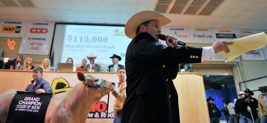 Auctioneer C. Jason Spence works at driving the price up during the San Antonio Stock Show and Rodeo Auction Saturday. The Grand champion steer owned by Braeden Raub (behind) sold for $125,000. Photo: For The San Antonio Express-News