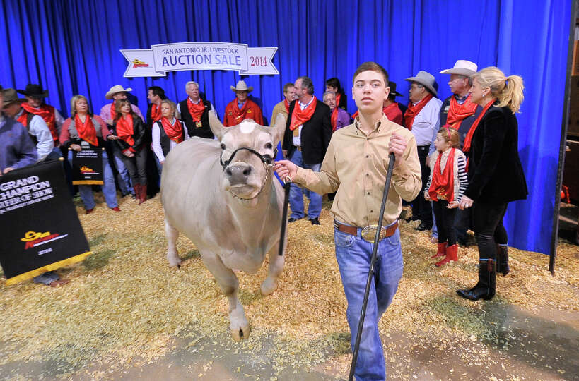 Braeden Raub, Lampasas walks with his Grand Champion Steer, Beaver, after he sold for $125,000 durin