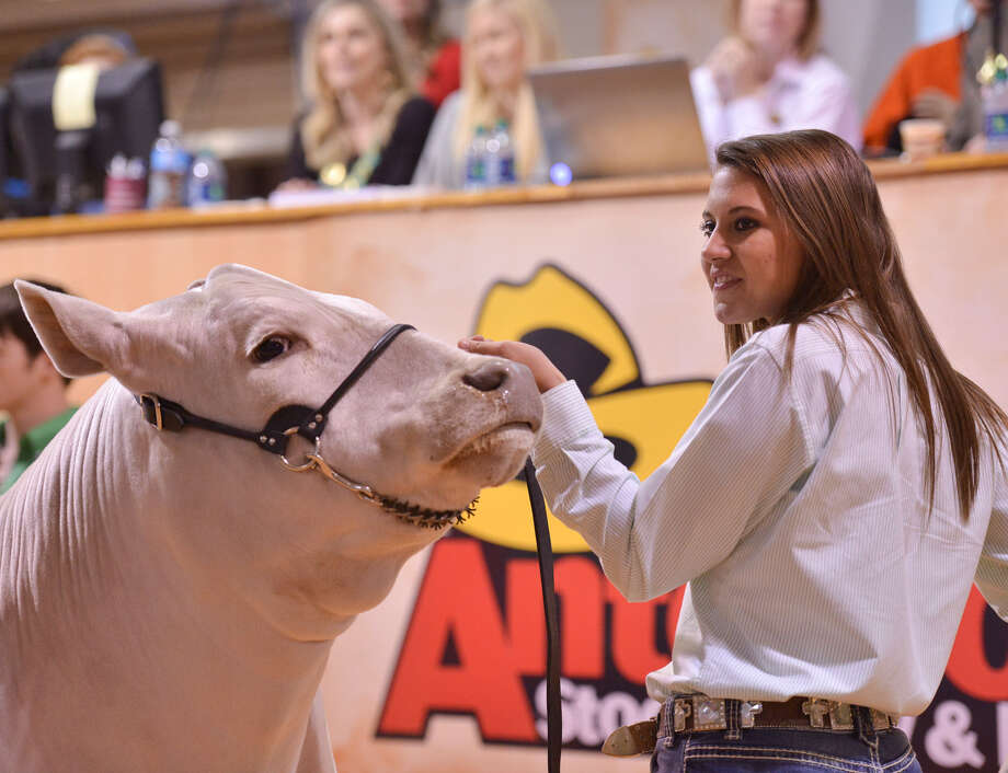 LEFT: Ashley Bradley, 16, of Boerne, sold her reserve grand champion, Tonto, for $78,000 Saturday during the San Antonio Stock Show and Rodeo Auction. RIGHT: Cameron Bargfrede, of the Seguin FFA, sings the national anthem to start the grand champion auction Saturday.