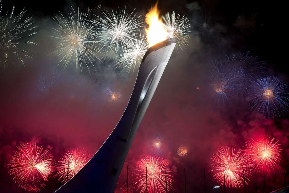 Fireworks explode behind the Olympic torch after it was lit at end of the opening ceremony for the 2014 Winter Olympics in Sochi, Russia, Friday, Feb. 7, 2014.  Photo: Bernat Armangue, Associated Press
