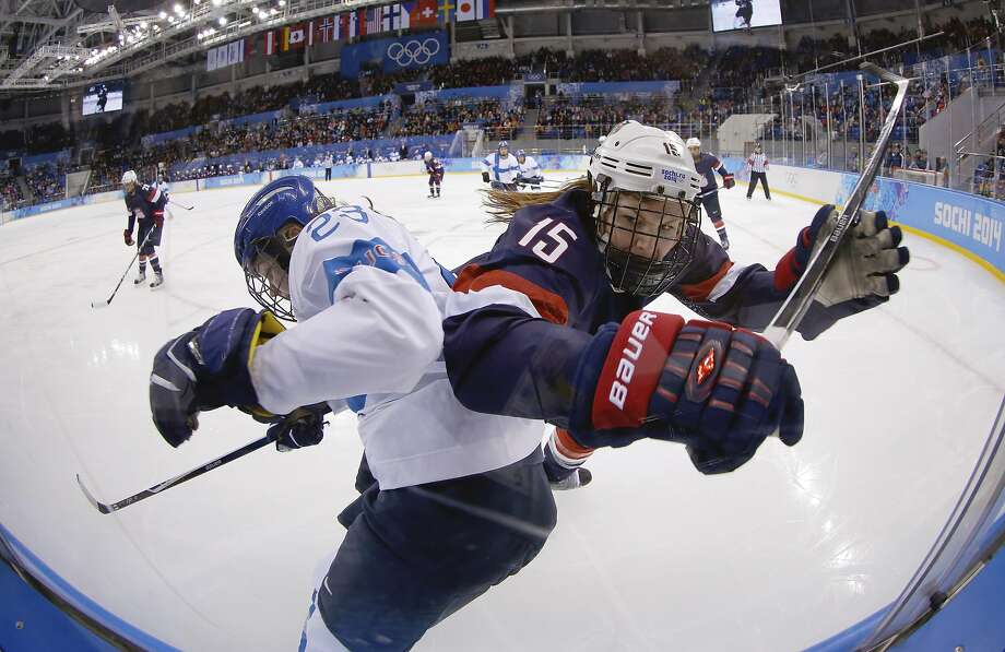 Nina Tikkinen of Finland and Anne Schleper of the United States battlers from control of the puck against the glass during the second period of the women's ice hockey game at the Shayba Arena during the 2014 Winter Olympics, Saturday, Feb. 8, 2014, in Sochi, Russia.  Photo: Matt Slocum, Associated Press