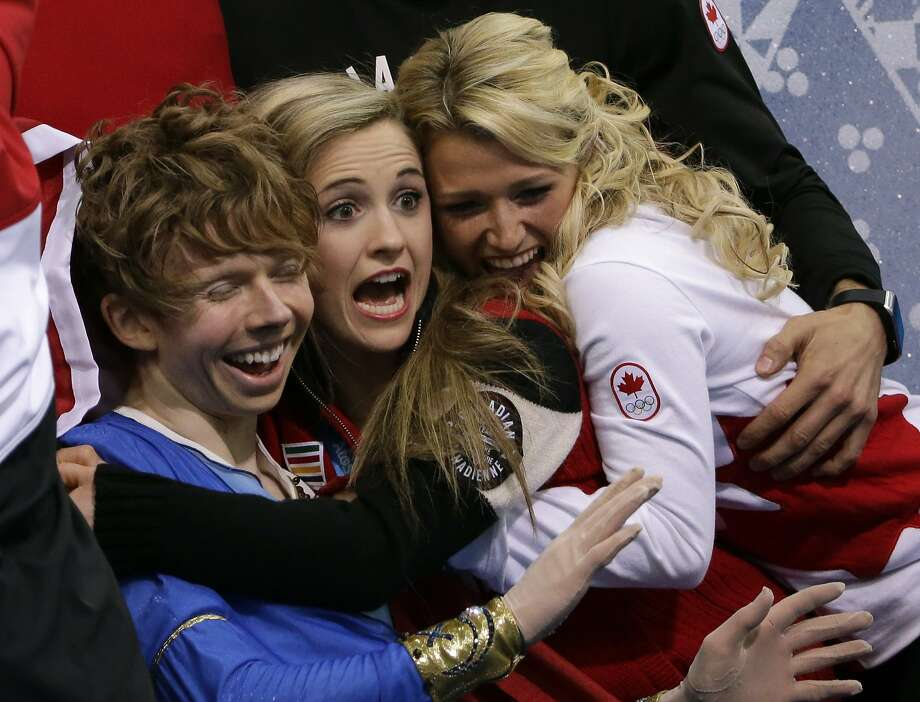 Kevin Reynolds of Canada, left, and team members react as he sits in the results area after competing in the men's team free skate figure skating competition at the Iceberg Skating Palace during the 2014 Winter Olympics, Sunday, Feb. 9, 2014, in Sochi, Russia.  Photo: David J. Phillip, Associated Press