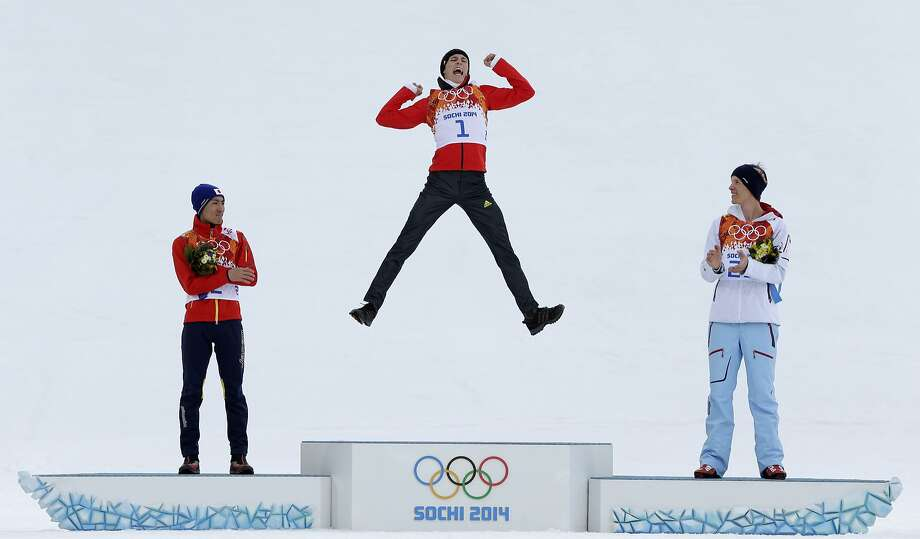 Germany's Eric Frenzel celebrates winning the gold as he is flanked by Japan's silver medal winner Akito Watabe, left, and Norway's bronze medal winner Magnus Krog  during the flower ceremony after the cross-country portion of the nordic combined at the 2014 Winter Olympics, Wednesday, Feb. 12, 2014, in Krasnaya Polyana, Russia. Photo: Matthias Schrader, Associated Press