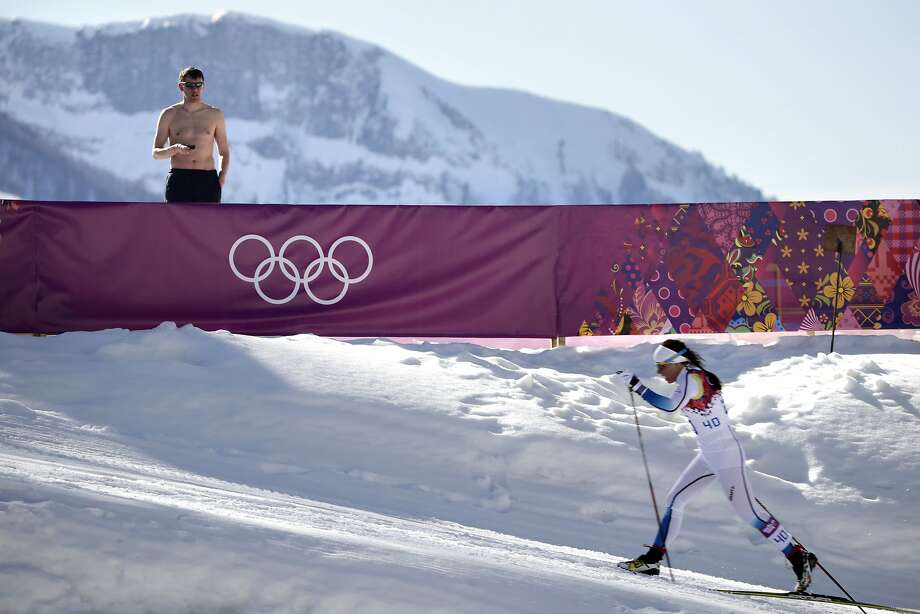 A shirtless spectator watches Sweden's Charlotte Kalla compete during the women's 10K classical style cross-country race at the 2014 Winter Olympics, Thursday, Feb. 13, 2014, in Krasnaya Polyana, Russia. Kalla won the silver medal. Photo: Jae C. Hong, Associated Press