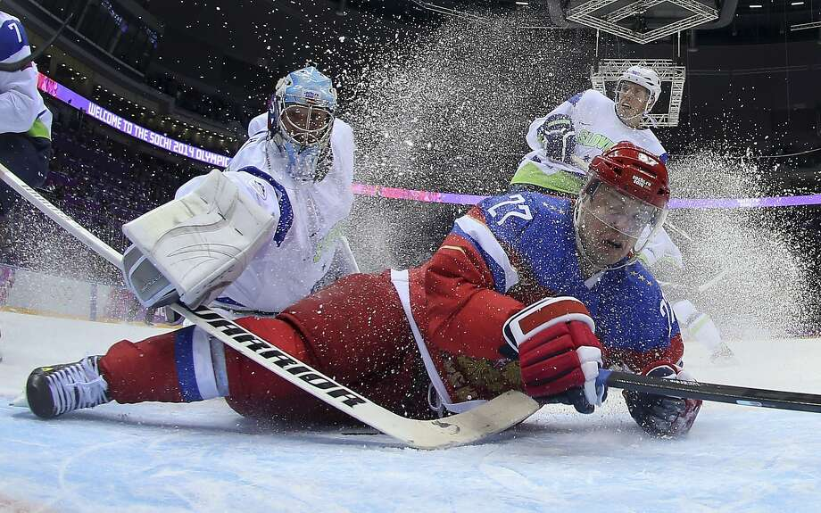 Slovenia goaltender Robert Kristan reaches over Russia forward Alexei Tereshenko as they fall to the ice at the goal in the first period of a men's ice hockey game at the 2014 Winter Olympics, Thursday, Feb. 13, 2014, in Sochi, Russia. Russia won 5-2.  Photo: Bruce Bennett, Associated Press