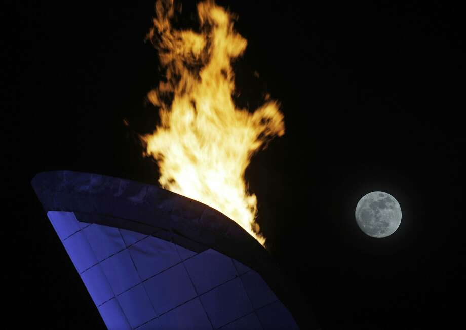 The moon is seen rising past the flame from the Olympic cauldron at the 2014 Winter Olympics, Thursday, Feb. 13, 2014, in Sochi, Russia.  Photo: Morry Gash, Associated Press