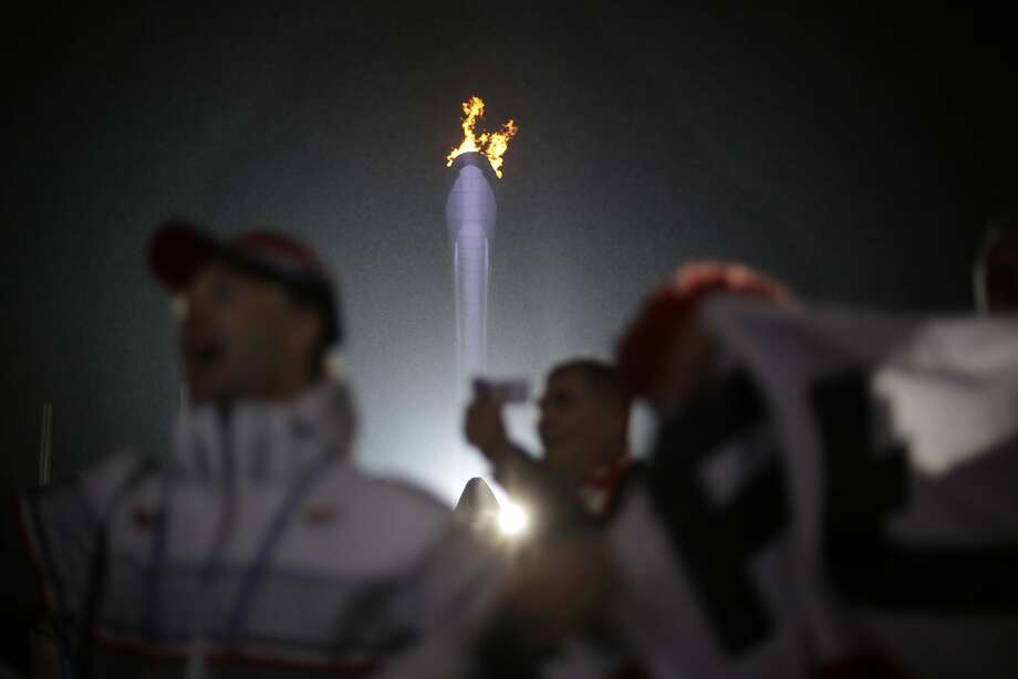 Fans cheer near the Olympic flame while watching the medals ceremonies at the 2014 Winter Olympics, Sunday, Feb. 16, 2014, in Sochi, Russia.  Photo: David Goldman, Associated Press