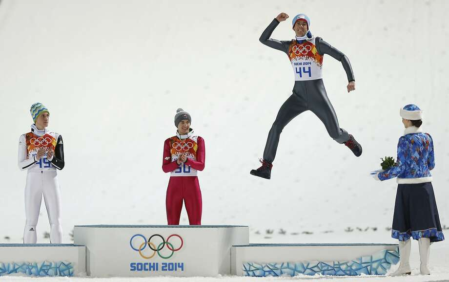 Norway's bronze medal winner Anders Bardal  jumps onto the podium as Slovenia's silver medal winner Peter Prevc, left, and Poland's gold medal winner Kamil Stoch, center, applaud after the men's normal hill ski jumping final at the 2014 Winter Olympics, Sunday, Feb. 9, 2014, in Krasnaya Polyana, Russia. (AP Photo/Matthias Schrader) Photo: Matthias Schrader, Associated Press