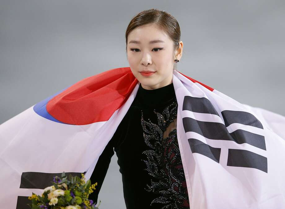Yuna Kim of South Korea celebrates her second place with the national flag following the flower ceremony for the women's free skate figure skating finals at the Iceberg Skating Palace during the 2014 Winter Olympics, Thursday, Feb. 20, 2014, in Sochi, Russia. (AP Photo/Vadim Ghirda) Photo: Vadim Ghirda, Associated Press