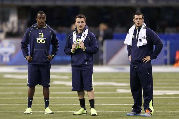 Former Louisville quarterback Teddy Bridgewater, former Fresno State quarterback Derek Carr and former Texas A&M quarterback Johnny Manziel look on during NFL combine drills.
