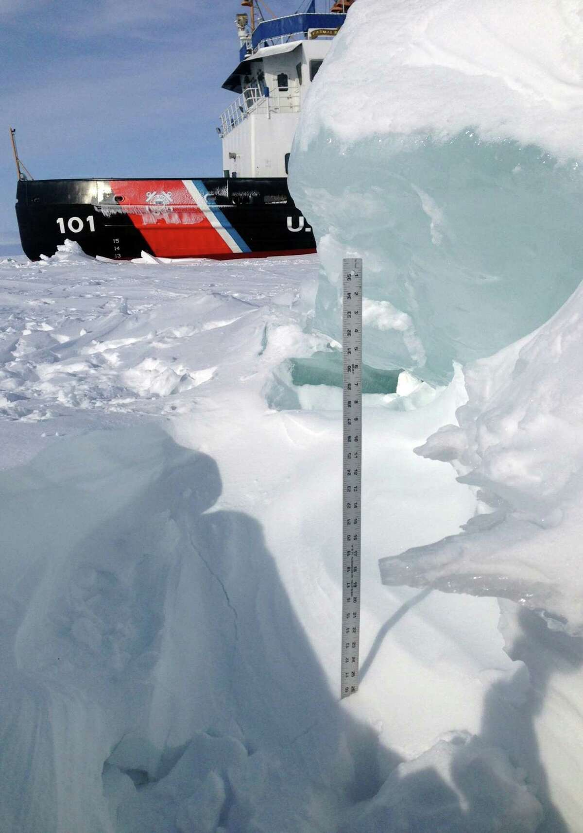A yardstick shows the thick ice the cutter Katmai Bay fights in the Straits of Mackinac.