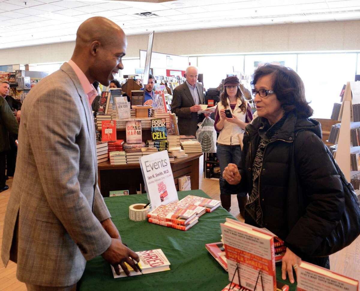 """Dr. Ian Smith a #1 New York Times and Amazon bestselling author and Danbury native was at Barnes & Noble for a special book signing for his newest diet book, """"Super Shred!"""". Smith signs a book for Myrtle Robs from Danbury on Saturday, Feb. 22, 2014."""