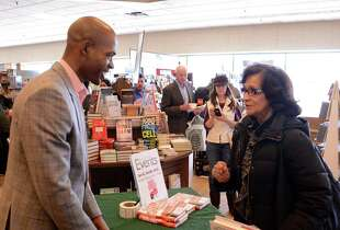 "Dr. Ian Smith a #1 New York Times and Amazon bestselling author and Danbury native was at Barnes & Noble for a special book signing for his newest diet book, ""Super Shred!"". Smith signs a book for Myrtle Robs from Danbury on Saturday, Feb. 22, 2014."