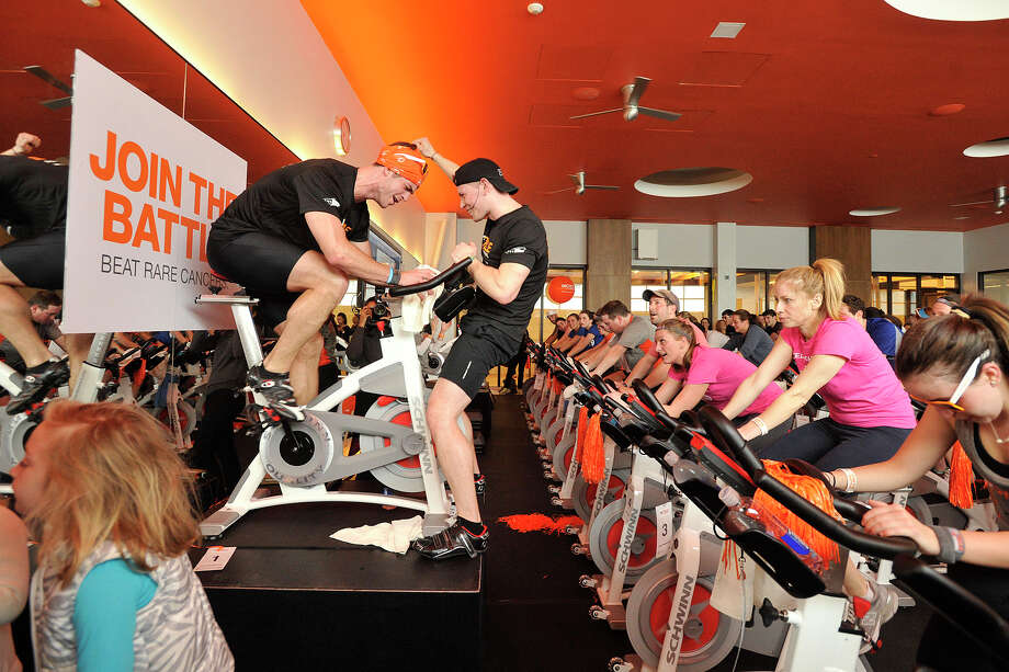 Chris Konopka, center, stands in front of Webb Travis trying to pump up the crowd of cyclists during the Cycle for Survival event benefiting Memorial Sloan Kettering Cancer Center at Equinox fitness center in Greenwich, Conn., on Sunday, Feb. 23, 2014. Nationally, Cycle for Survival has raised over $47 million for rare cancer research. Photo: Jason Rearick / Stamford Advocate