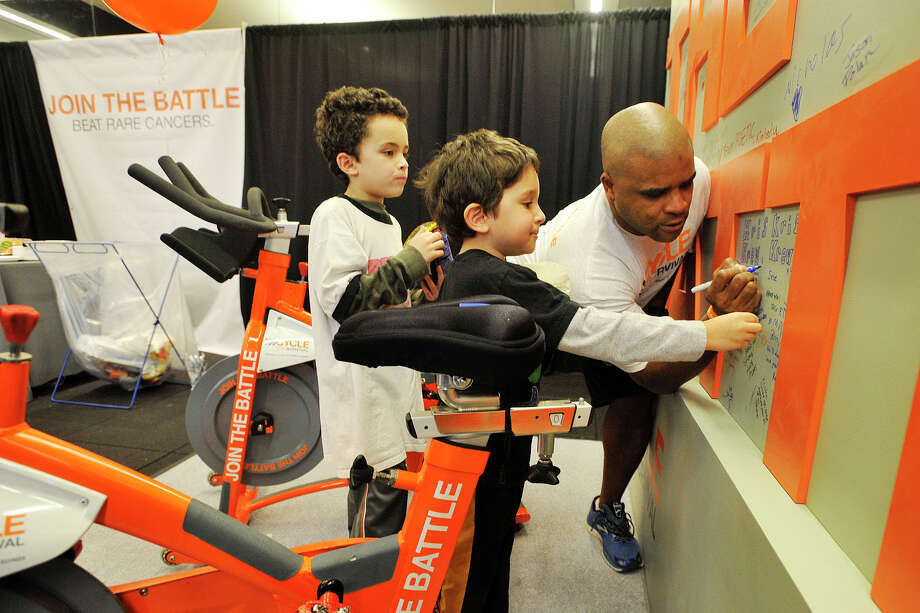 Cameron Rice writes on a memorial wall as his sons, Cameron Rice Jr, left, and Emmett Rice, look on during the Cycle for Survival event benefiting Memorial Sloan Kettering Cancer Center at Equinox fitness center in Greenwich, Conn., on Sunday, Feb. 23, 2014. The Rice's were from the team Kris' Krew in memory of a friend that died. Nationally, Cycle for Survival has raised over $47 million for rare cancer research. Photo: Jason Rearick / Stamford Advocate