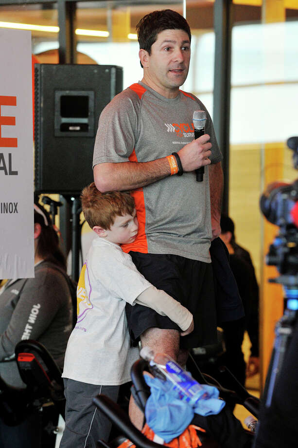 Omar Mureebe speaks about a loved one he lost as his son, Owen, hugs his leg during the Cycle for Survival event benefiting Memorial Sloan Kettering Cancer Center at Equinox fitness center in Greenwich, Conn., on Sunday, Feb. 23, 2014. Nationally, Cycle for Survival has raised over $47 million for rare cancer research. Photo: Jason Rearick / Stamford Advocate
