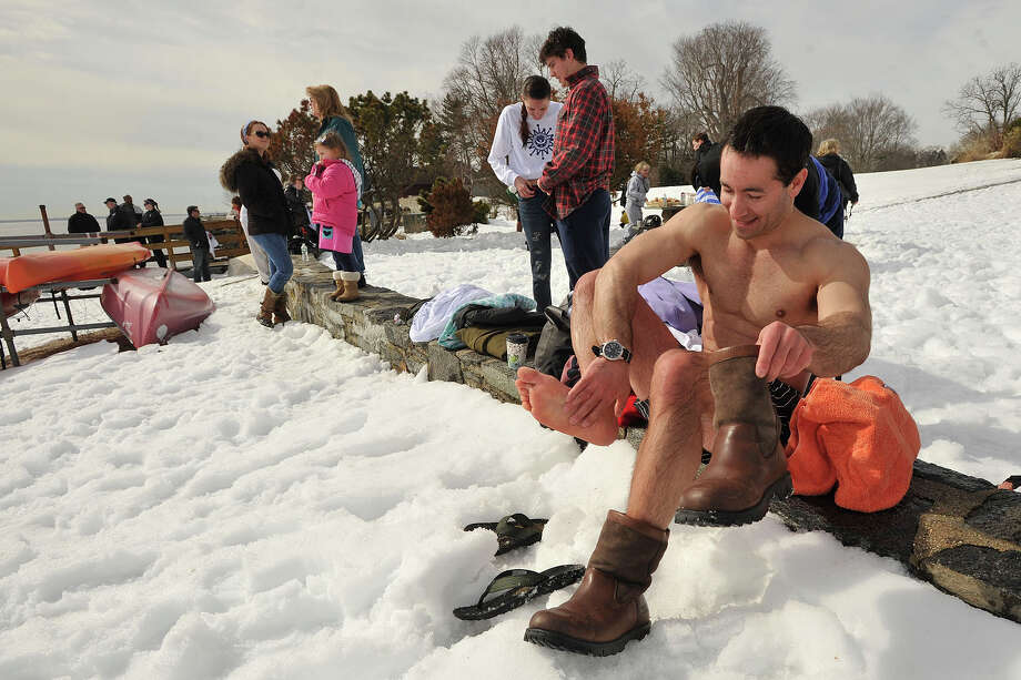 Eric West, right, dresses in the snow after participating in the third annual Polar Bear Plunge benefiting Family Centers at Geneve Holdings in Stamford, Conn., on Sunday, Feb. 23, 2014. Photo: Jason Rearick / Stamford Advocate