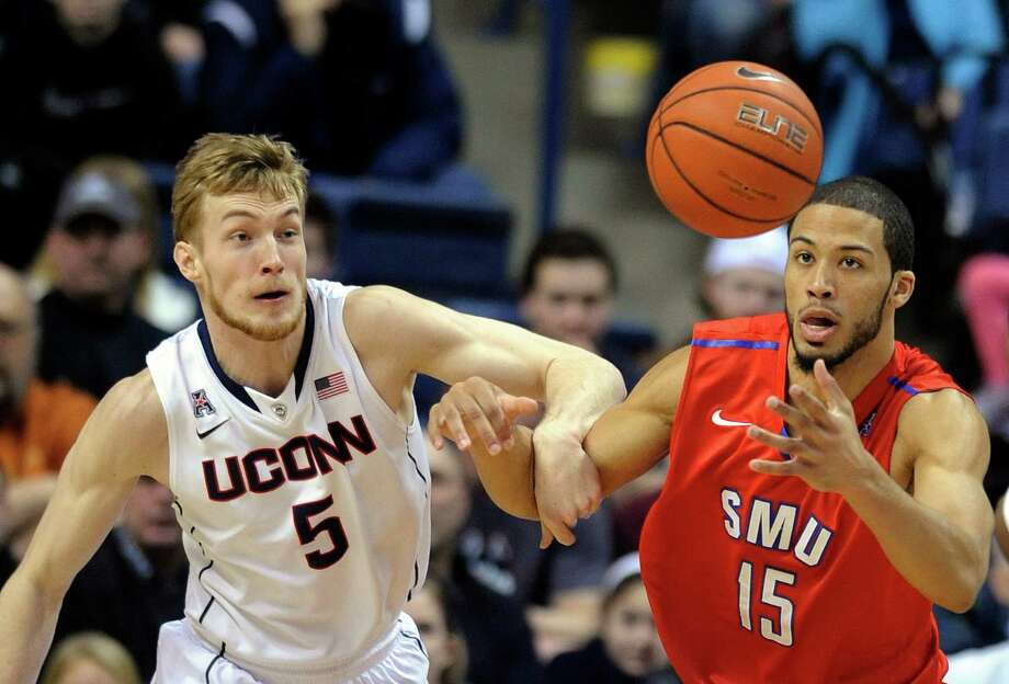 Connecticut's Niels Giffey (5) and SMU's Cannen Cunningham (15) fight for the loose ball during the first half of an NCAA college basketball game in Storrs, Conn., Sunday, Feb. 23, 2014. Photo: Fred Beckham, AP / Associated Press