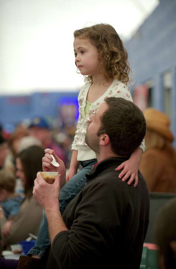 Chris McCann, of Bethel, looks at his daughter Lilly McCann, age 6, as she watches the Danbury High School cheerleaders perform during the Sixth Annual Chili Winter Warm Up at the Danbury Sports Dome on Sunday, February 23, 2014, in Danbury, Conn. Photo: H John Voorhees III / The News-Times Freelance