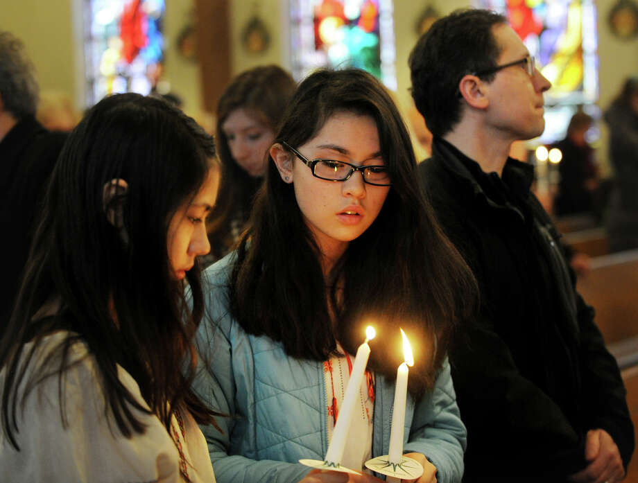 From left; Emily, 12, Hanna, 13, and Adam Trojanowski, of Redding, light candles during a memorial service for the Ukrainian dead at St. Michael's Ukrainian Church in New Haven, Conn. on Sunday, February 23, 2014. Photo: Brian A. Pounds / Connecticut Post