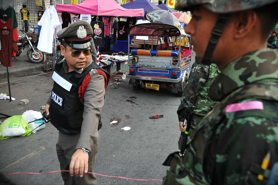 Soldiers and police gather at the site of a Bangkok grenade blast that killed a woman and two children. Photo: Rufus Cox, Getty Images