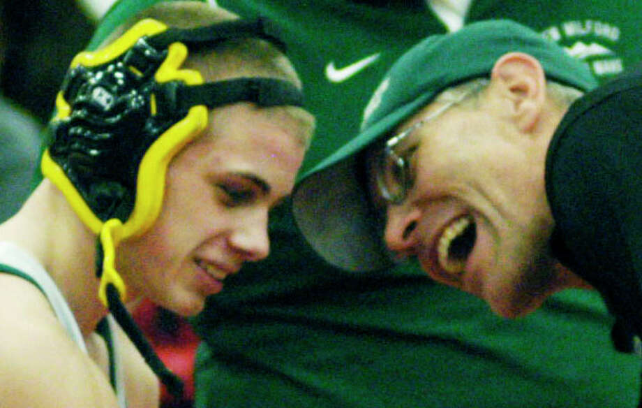 The Green Wave's C.J. Schulz is given a rousing greeting by coach Chris Piel after outwrestling Ben Reilly of New Fairfield to win the 120-pound weight class for New Milford High School wrestling during the South-West Conference championship tournament at Pomperaug High School in Southbury, Feb.16, 2014. Photo: Norm Cummings / The News-Times