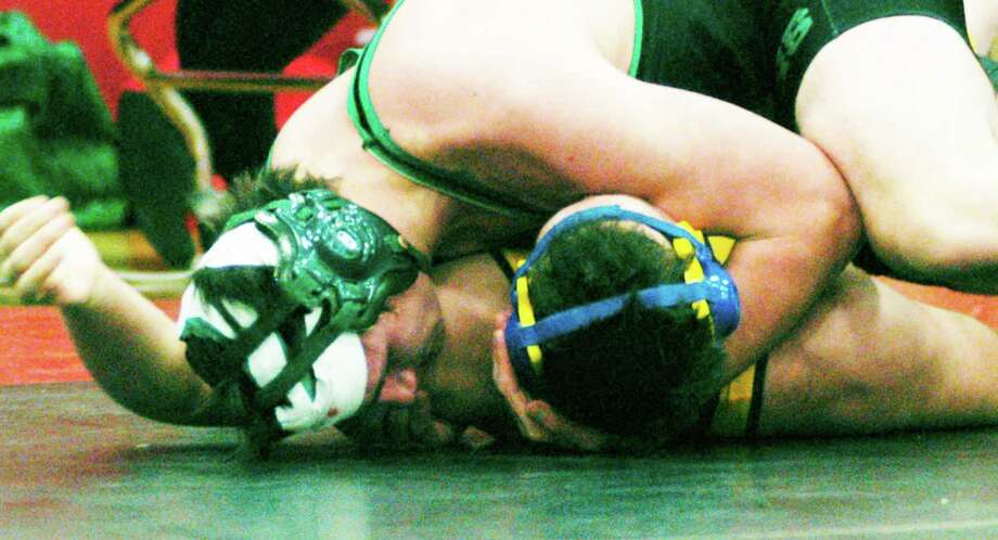 Tom McIlveen of the New Miford High School wrestling team scores this clutch pin of Newtown's Ryan Wagner late in the third period of the 220-pound title bout to deliver the Green Wave's eighth straight South-West Conference team championship. Photo: Norm Cummings / The News-Times